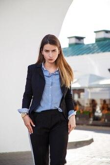 Schönes frauenporträt mit langen gesunden haaren. modischer damenlook mit schwarzer jacke und blauer bluse