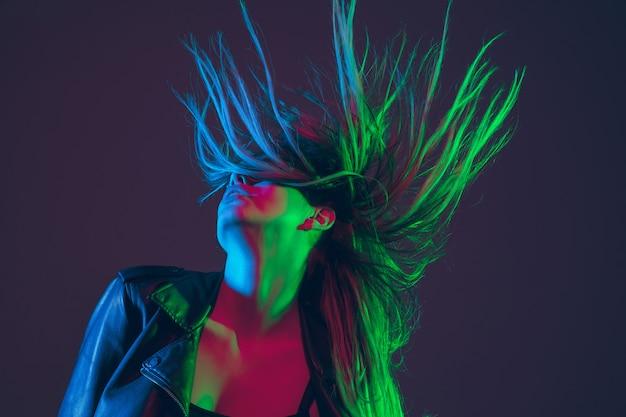 Schönes frauenporträt mit wehendem haar im bunten neonlicht