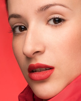 Schönes frauenportrait auf rotem hintergrund