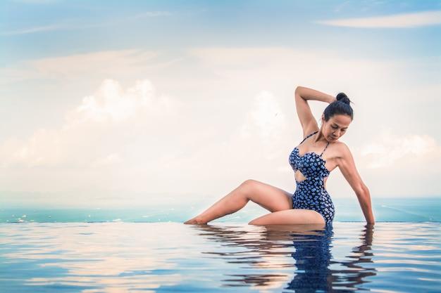 Schönes frauenyoga im türkisblauen schwimmbad.