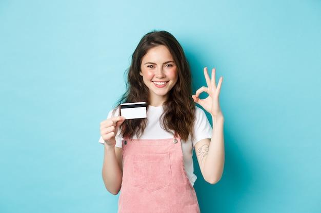 Schönes freches mädchen, das plastikkreditkarte empfiehlt, ein okayzeichen zeigt und selbstbewusst in die kamera schaut, zufrieden lächelt und auf blauem hintergrund steht
