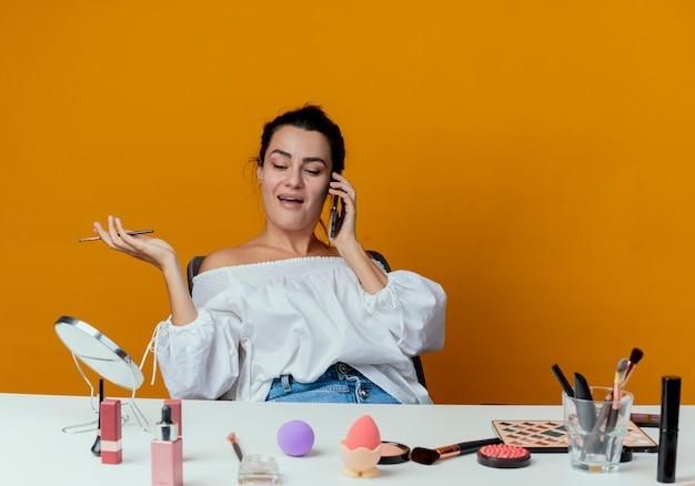 Schönes freudiges mädchen sitzt am tisch mit make-up-werkzeugen spricht am telefon, das make-up-pinsel lokalisiert auf orange wand hält