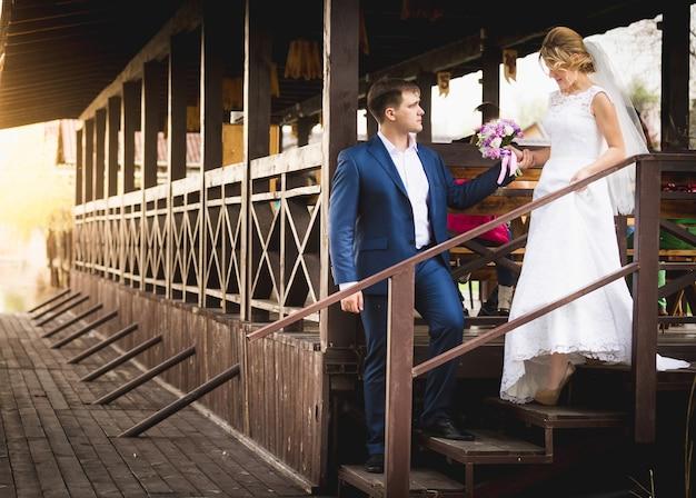 Schönes frisch verheiratetes paar, das bei sonnenuntergang auf dem liegeplatz posiert