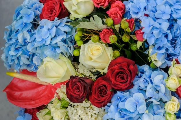 Schönes frisches helles bouquet von blauen hortensien, roten und cremefarbenen rosen. schöne blumenkomposition.