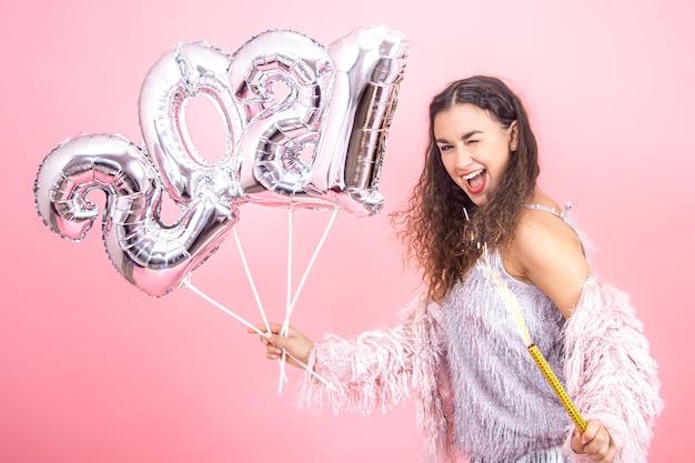 Schönes fröhliches festlich gekleidetes brünettes mädchen mit lockigem haar auf einer rosa wand zwinkert mit silbernen luftballons für das neujahrskonzept