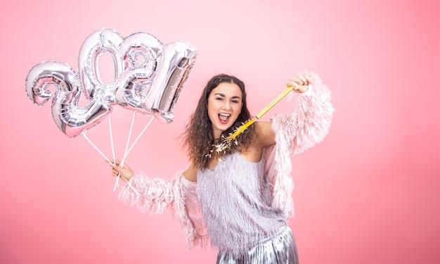 Schönes fröhliches festlich gekleidetes brünettes mädchen mit lockigem haar, das auf einem rosa studiohintergrund mit silbernen luftballons für das neujahrskonzept aufwirft