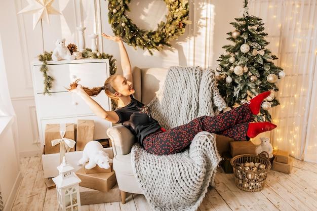 Schönes fröhliches glückliches junges mädchen im schlafanzug mit weihnachtsgeschenken auf sofa auf dem hintergrund eines neujahrsbaums zu hause