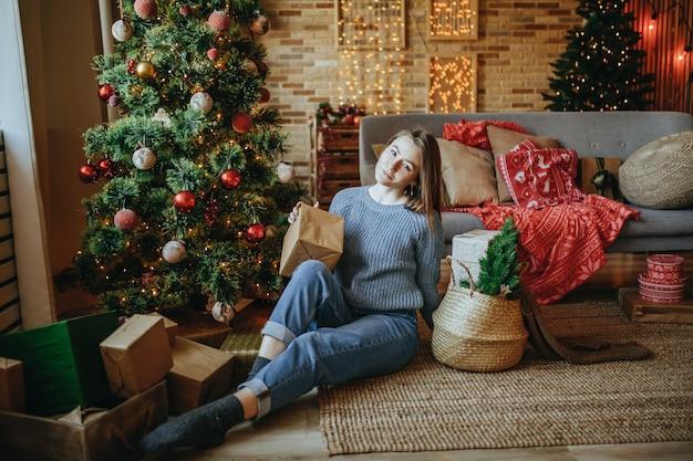 Schönes fröhliches glückliches junges mädchen mit weihnachtsgeschenken auf dem boden nahe dem neujahrsbaum zu hause