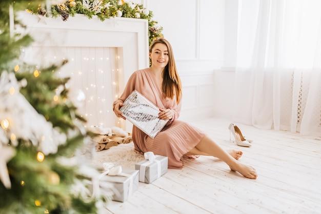 Schönes fröhliches glückliches junges mädchen mit weihnachtsgeschenken auf dem hintergrund eines neujahrsbaums zu hause