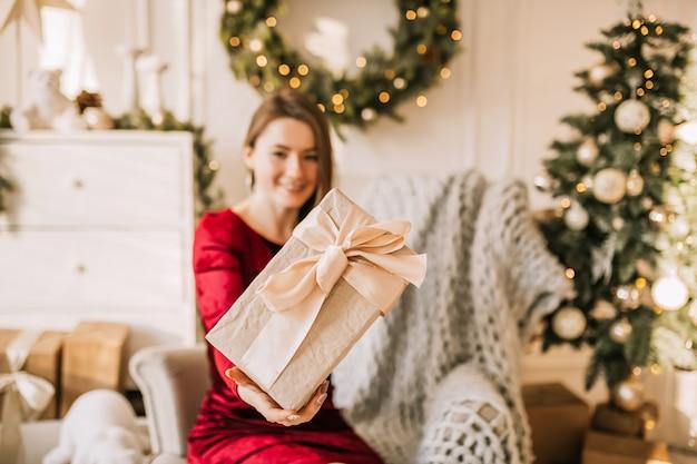Schönes fröhliches glückliches junges mädchen mit weihnachtsgeschenken auf sofa auf dem hintergrund eines neujahrsbaums zu hause