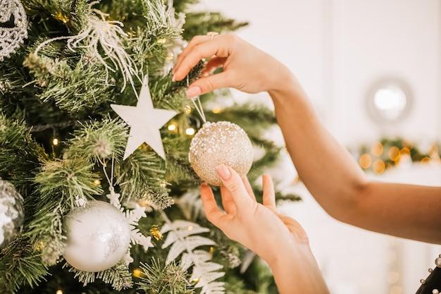 Schönes fröhliches glückliches junges mädchen schmücken neujahrsbaum-weihnachtsspielzeug zu hause