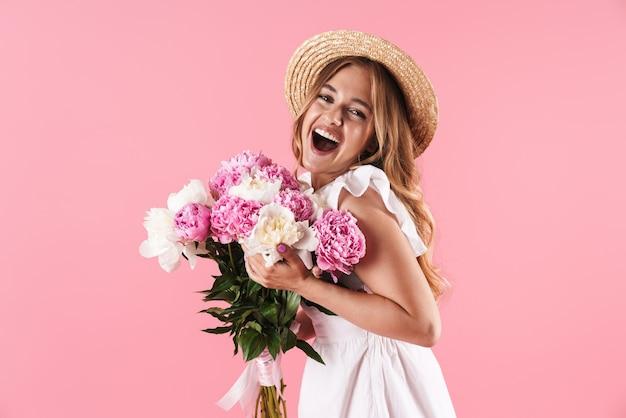 Schönes fröhliches junges blondes mädchen, das sommerkleid trägt, das isoliert über rosa wand steht und einen strauß pfingstrosen hält