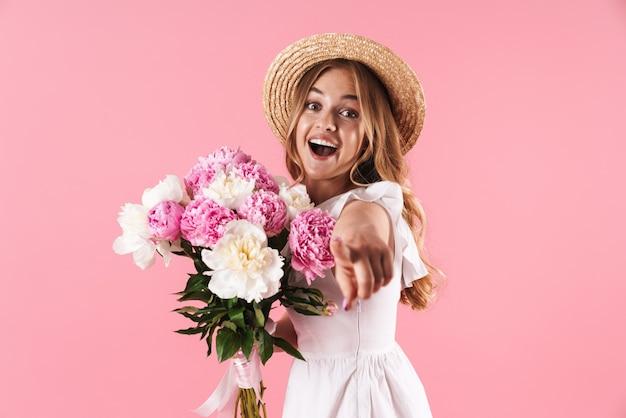 Schönes fröhliches junges blondes mädchen im sommerkleid, das isoliert über rosafarbener wand steht, einen strauß pfingstrosen hält und auf die kamera zeigt