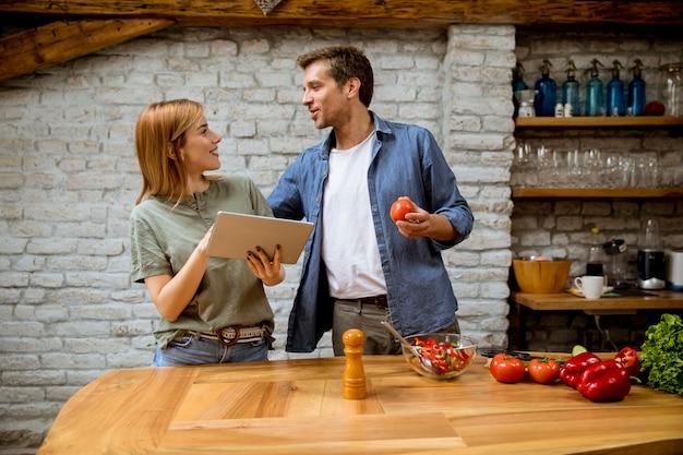 Schönes fröhliches junges paar, das abendessen zusammen kocht, rezept auf digitales tablett schaut und spaß an rustikaler küche hat