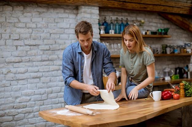 Schönes fröhliches junges paar, das abendessen zusammen vorbereitet und spaß an der rustikalen küche hat