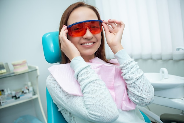 Schönes, fröhliches mädchen im stuhl des zahnarztes. zahnbehandlung. zahnarztklinik