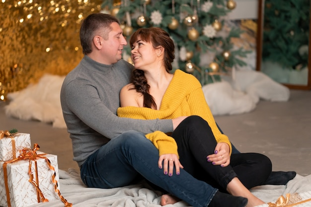 Schönes fröhliches paar begrüßt die weihnachtsferien in einer gemütlichen häuslichen atmosphäre