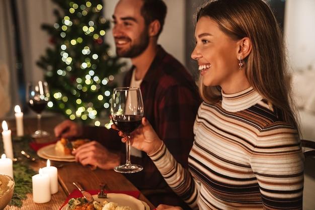 Schönes fröhliches paar, das wein trinkt und lacht, während es weihnachtsessen in einem gemütlichen zimmer hat?