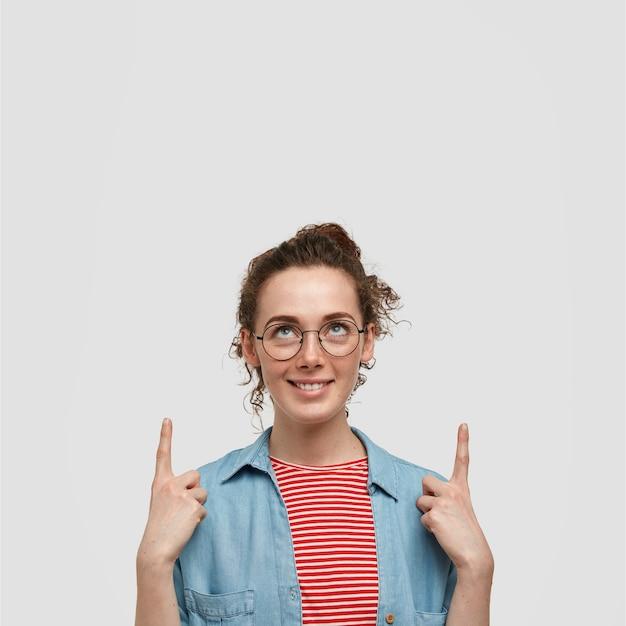 Schönes fröhliches weibliches model mit spezifischem aussehen, sieht positiv nach oben aus, zeigt mit zeigefingern, zeigt copyspace