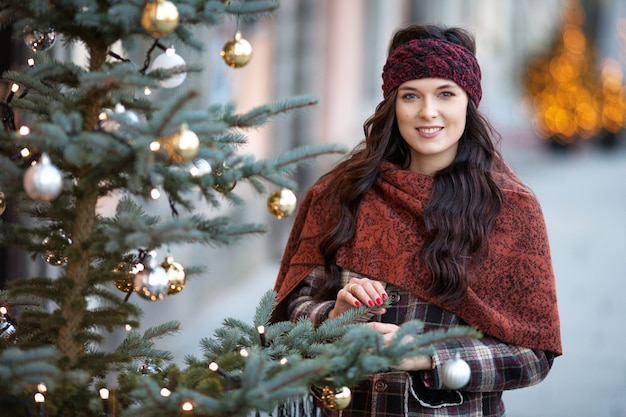 Schönes frohes frauenporträt in einer stadt. lächelndes mädchen, das warme kleidung und hut im winter trägt.