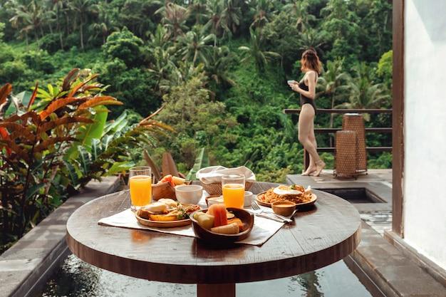 Schönes frühstück auf einem holztisch gegen das pool und eine junge schönheit in einem badeanzug mit einem tasse kaffee in der hand. frühstück mit blick auf den tropischen dschungel in bali