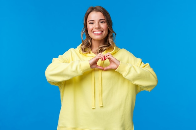 Schönes fürsorgliches süßes blondes mädchen im gelben kapuzenpulli, das herzgeste zeigt und als ausdruck symapthy lächelt, in liebe oder herzerwärmende gefühle gegenüber person bekennt, auf einer blauen wand stehen