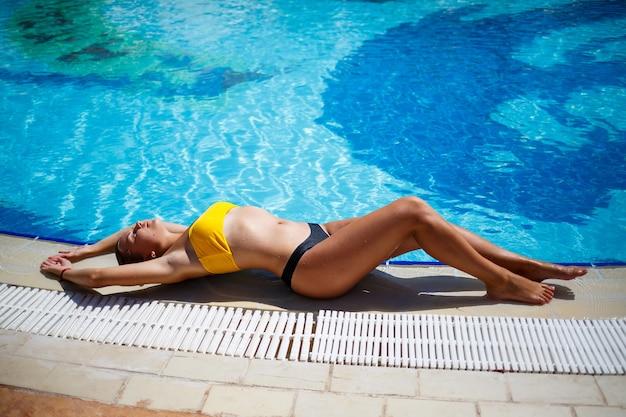 Schönes gebräuntes mädchen in einem gelben badeanzug in einem großen swimmingpool mit blauem wasser