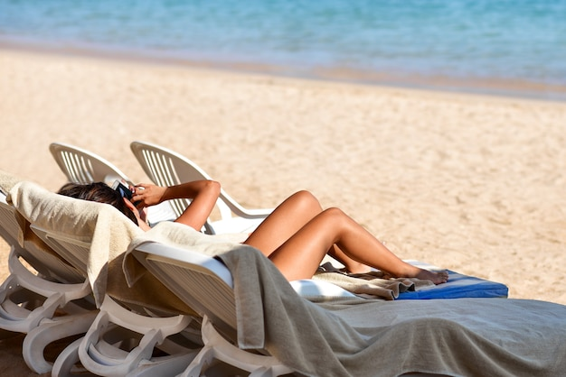 Schönes gebräuntes mädchen nimmt auf dem strand ein sonnenbad und untersucht einen smartphone