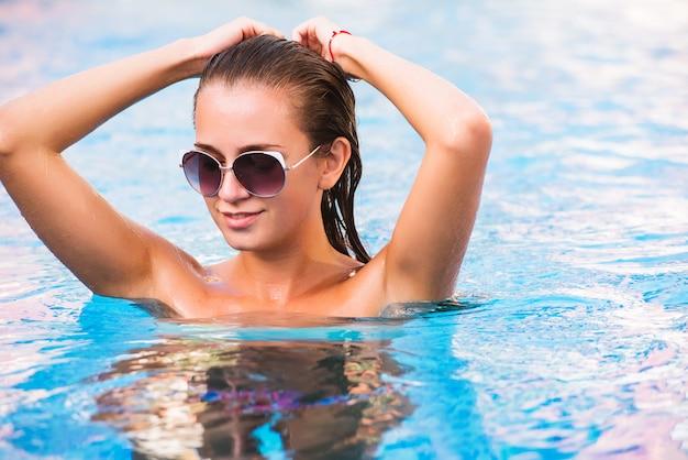Schönes gebräuntes sexy mädchen im bikini, der im swimmingpool aufwirft