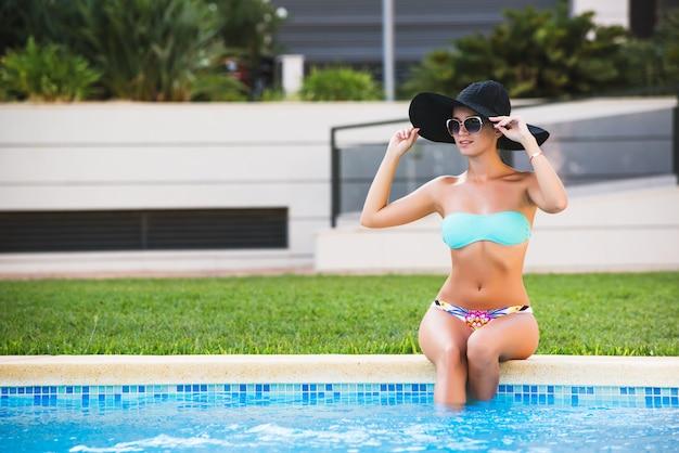 Schönes gebräuntes sexy mädchen im bikini und in schwarzem hut, die an einem swimmingpool ein sonnenbad nehmen