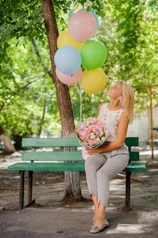 Schönes geburtstagsmädchen mit hübschen blumen und ballonen
