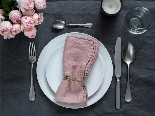 Schönes gedeck mit rosa sprayrosen und -kerze auf grauer leinentischdecke. festliches gedeck für hochzeitsabendessen mit rosa serviette auf platte. feiertagsabendessen mit weißen tellern