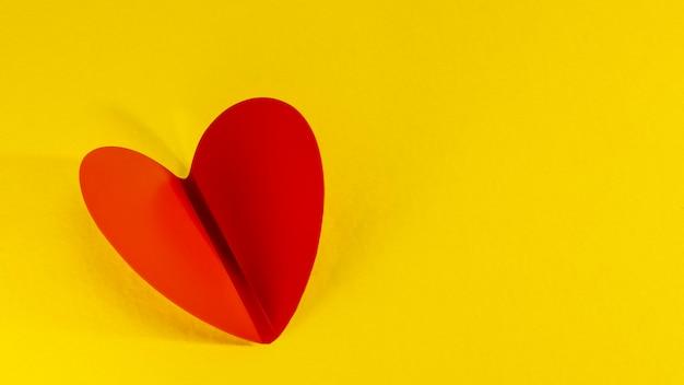 Schönes gefaltetes rotes herz auf gelbem grund. nahansicht. minimalismus. valentinstag.