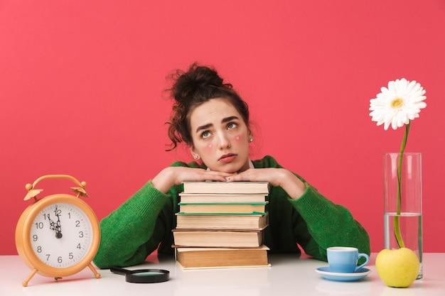 Schönes gelangweiltes junges studentenmädchen, das isoliert am tisch sitzt und mit büchern studiert