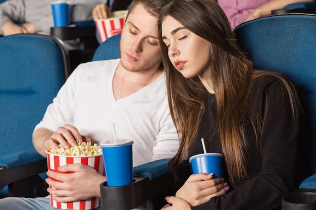 Schönes gelangweiltes paar, das während eines films im örtlichen kino schläft