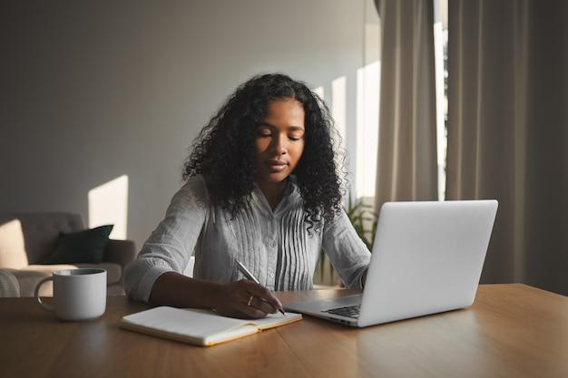 Schönes gemischtes rassenstudentenmädchen mit voluminöser frisur, die an hausaufgabe in ihrem zimmer arbeitet, am hölzernen schreibtisch sitzt, laptop verwendet und in heft schreibt. menschen, technologie und bildung