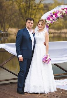 Schönes gerade verheiratetes paar, das auf verziertem pier bei hochzeitszeremonie steht standing