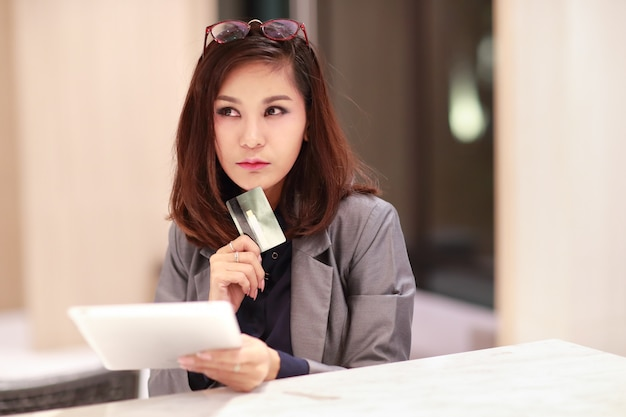 Schönes geschäftsfraueinkaufen und online-zahlung unter verwendung der tablette und der kreditkarten an hand