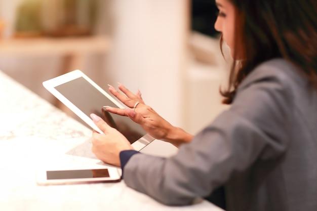 Schönes geschäftsfrauporträt unter verwendung der tablette (dieses bild für geschäfts- und technologiehintergrundkonzept)