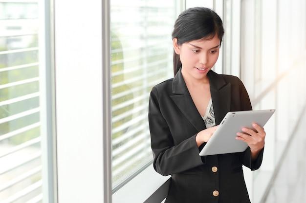 Schönes geschäftsfrauporträt unter verwendung der tablette
