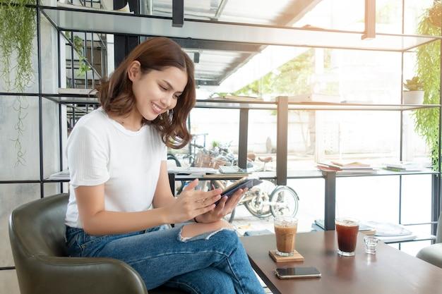 Schönes geschäftsmädchen, das mit tablette, smartphone arbeitet und kaffee in der kaffeestube trinkt