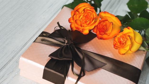 Schönes geschenk für den feiertag und ein blumenstrauß von orange rosen auf dem tisch