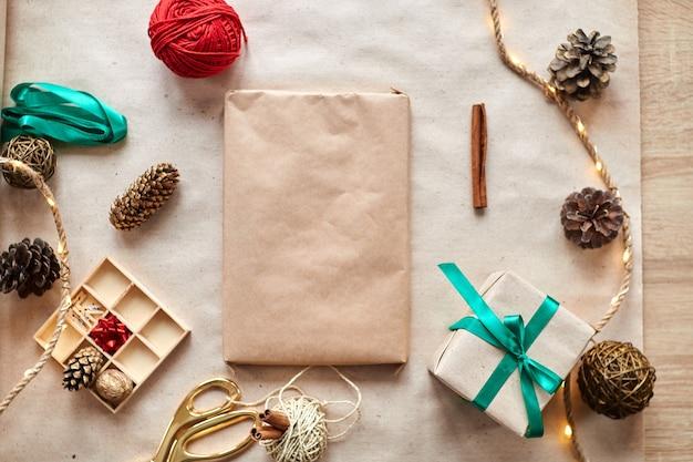 Schönes geschenk für weihnachten mit dekor auf holztisch. weihnachtsvorbereitung. winterferien. geschenkverpackung und dekorieren von weihnachtsgeschenken, schachteln aus bastelpapier mit satiniertem silberband.