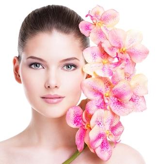 Schönes gesicht der jungen brünetten frau mit gesunder haut und rosa blumen nahe gesicht - lokalisiert auf weiß.