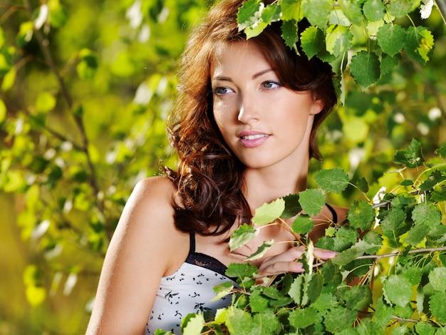 Schönes gesicht der jungen frau, die nahe dem grünen baum auf natur aufwirft