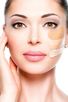 Schönes gesicht der jungen frau mit kosmetischer grundlage auf einer haut. schönheitsbehandlungskonzept