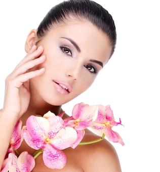 Schönes gesicht der jungen hübschen frau mit gesunder haut und rosa blumen auf körper - lokalisiert auf weiß