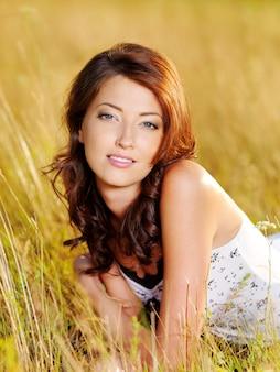Schönes gesicht der jungen sexy frau, die auf dem gras liegend aufwirft