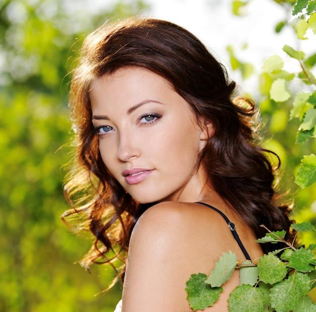 Schönes gesicht der jungen sexy frau, die nahe dem grünen baum auf natur aufwirft