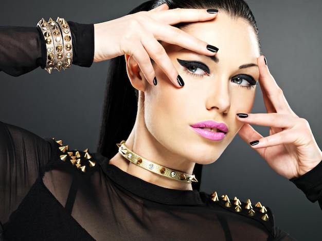 Schönes gesicht der modefrau mit schwarzen nägeln und hellem make-up. sexy stilvolles mädchen mit armband dornen am hals